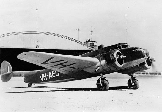 Stejné letadlo VH-AEC ve válečných barvách na letišti Archerfield v roce 1942. Dobře patrné je jméno Inlander na přídi. Podobný kamuflážní nátěr nosily za války i nkteré další australské letouny Elecgtra (foto Quantas Heritage Collection/Len Dobbin, via Ron Cuskelly)